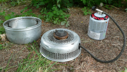 Picture of Gas burner in Trangia base with upper windshield beside