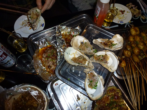 Chengdu barbecue feast: pig's brains (in the tinfoil), oysters, and a variety of things on sticks.