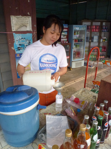 Recycling!  A used water bottle being re-filled with 'laolao' (Laos whisky).