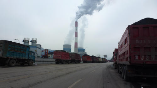 Brimming coal trucks delivering into a power station