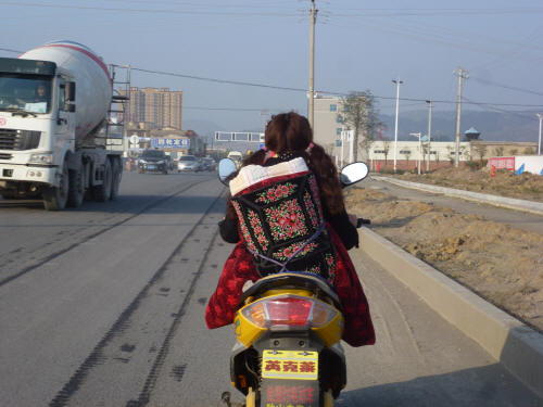 The brightly coloured ruck-sack is actually a child-carrier, likely embroidered by hand by the wearer